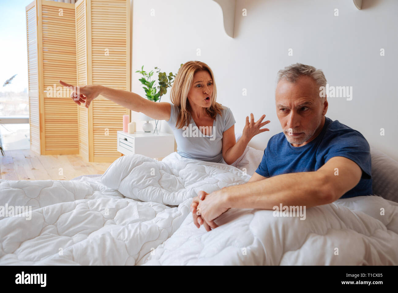 Emotional woman yelling at her husband after betrayal - Stock Image