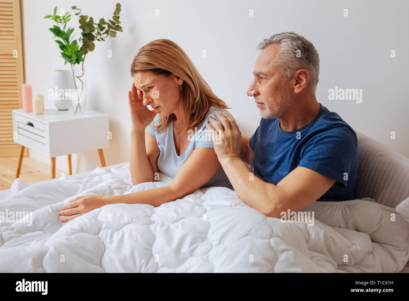 Blonde woman having headache after argument with husband - Stock Image