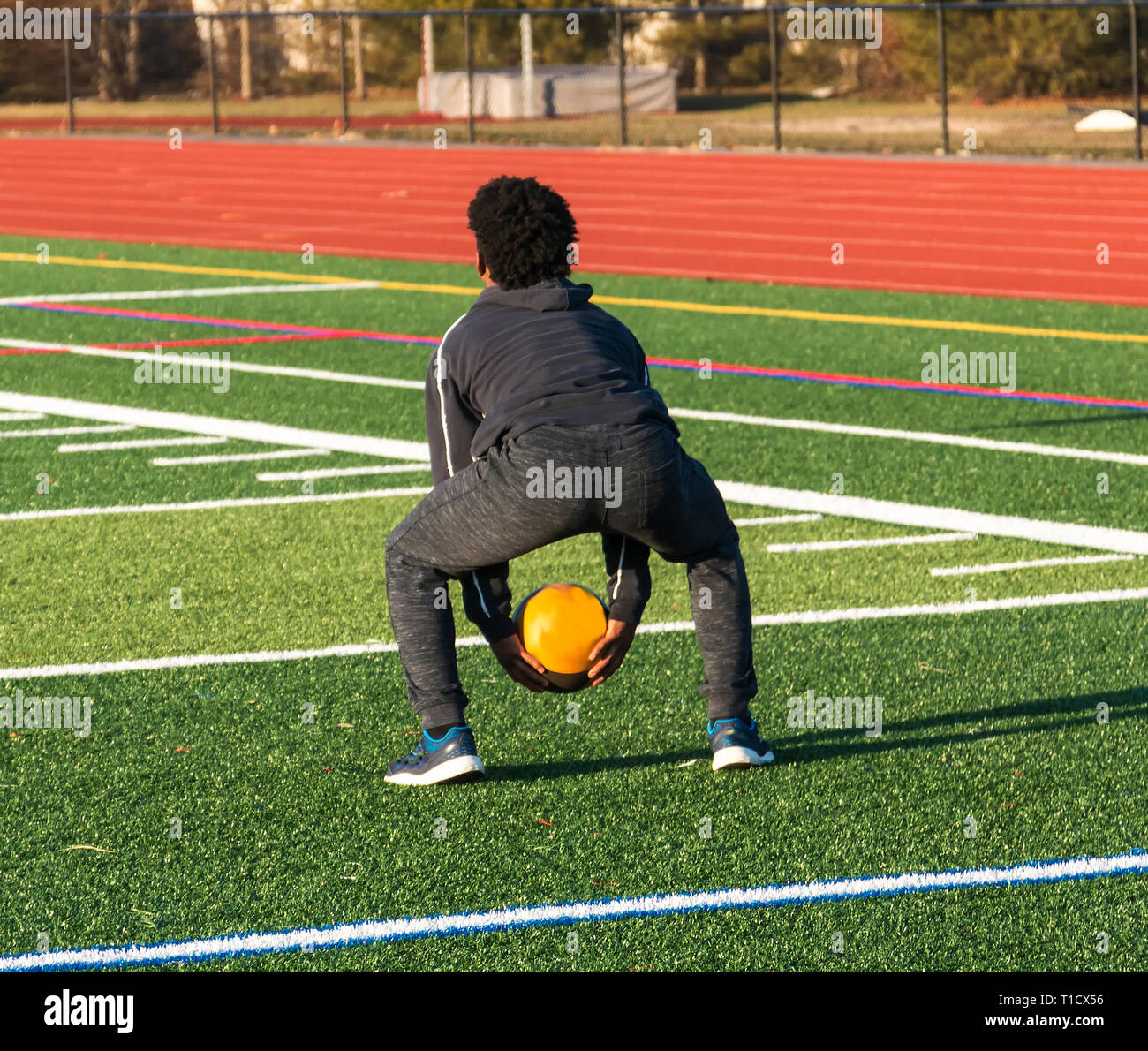 A high school track and field athlete is squatting down ready to throw a medicine ball over his head during speed and strength practice. - Stock Image
