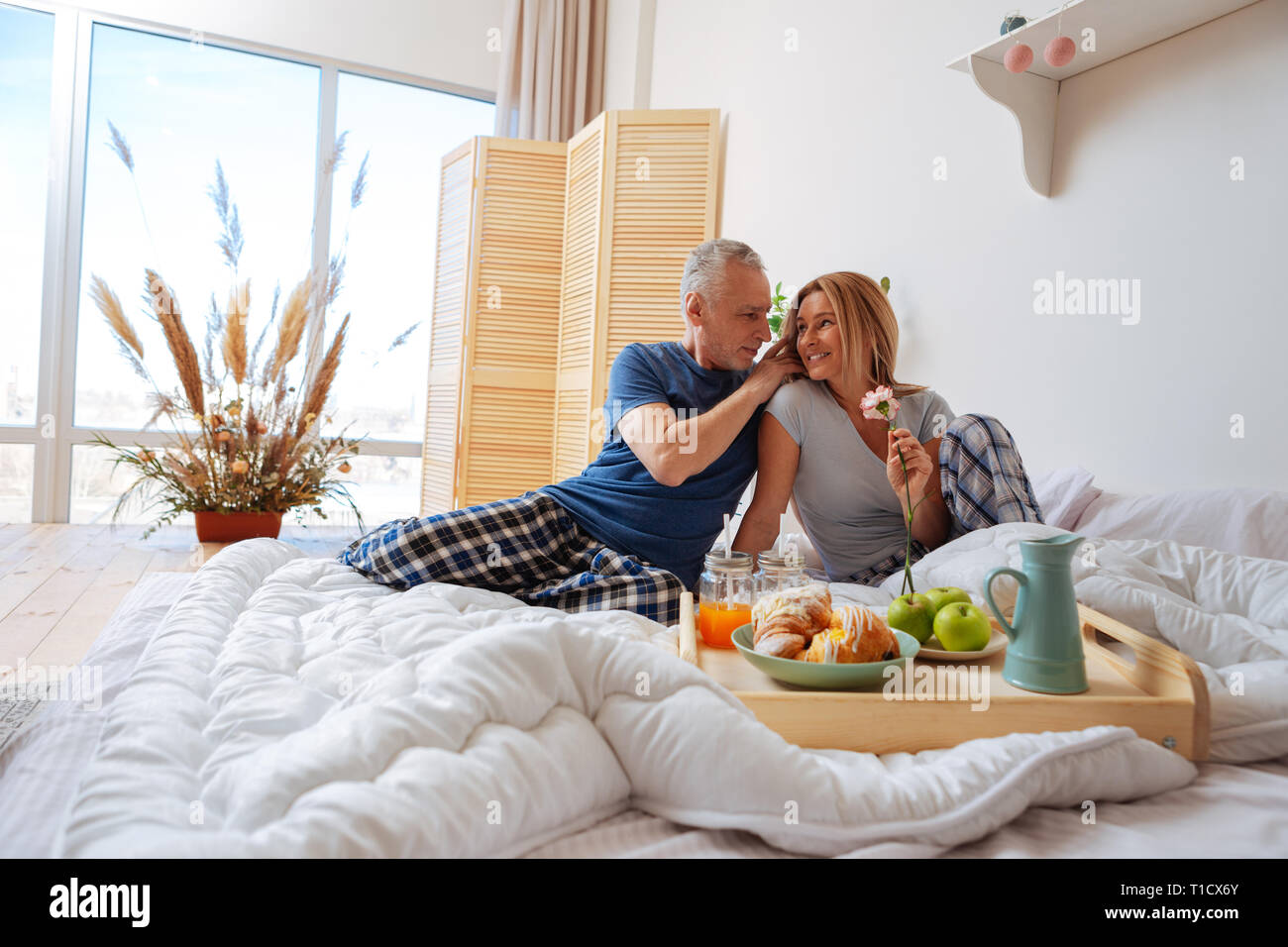 Wife feeling happy after receiving flower and breakfast in bed - Stock Image