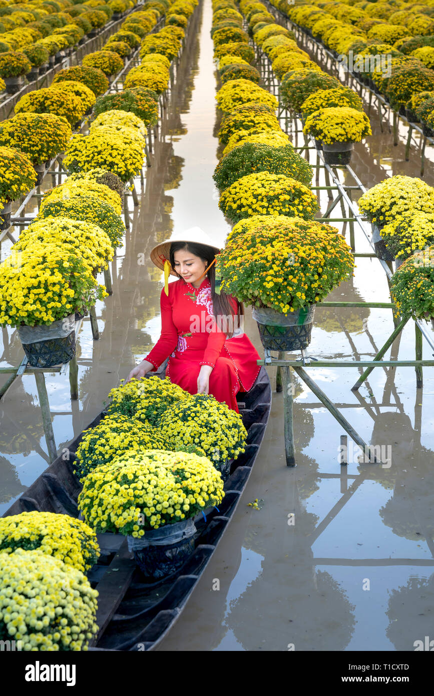 Sa Dec Flower Village , Sa Dec town, Dong Thap province, Vietnam - January 27, 2019: The young girls wearing Vietnamese traditional clothing - Stock Image