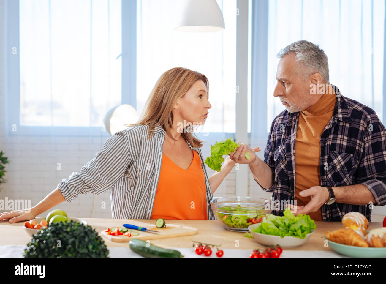 Emotional couple having argument while cooking salad for lunch - Stock Image