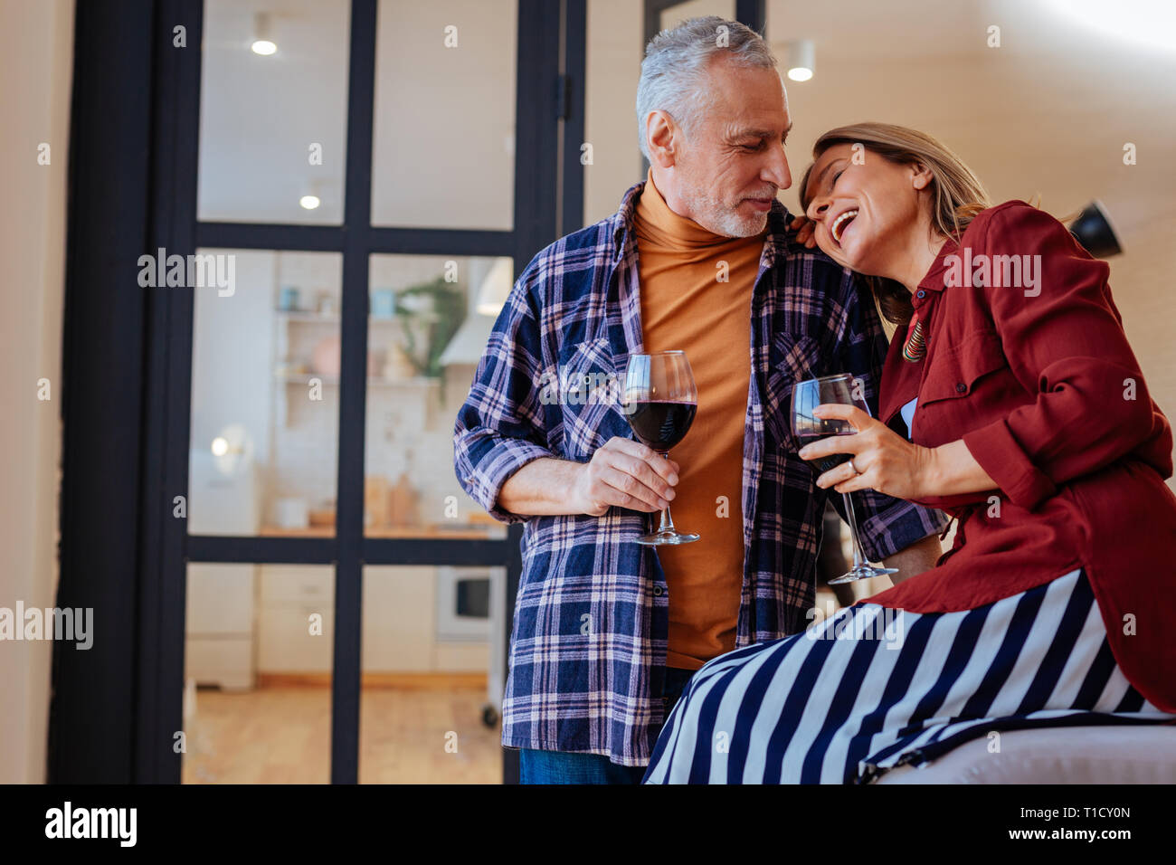 Cheerful laughing wife leaning on shoulder of her husband Stock Photo