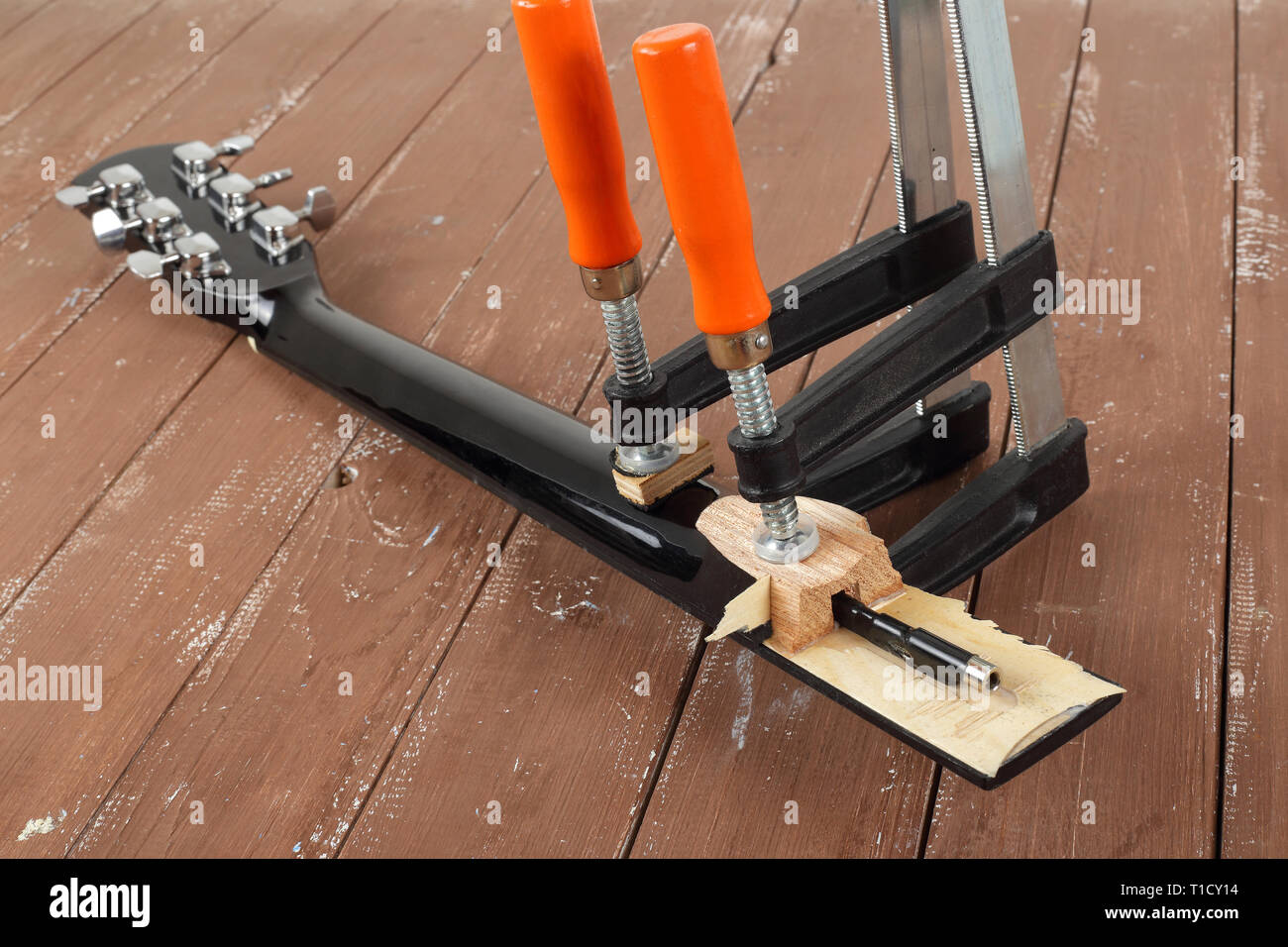 Guitar repair and service - Clamping a guitar neck wooden background - Stock Image
