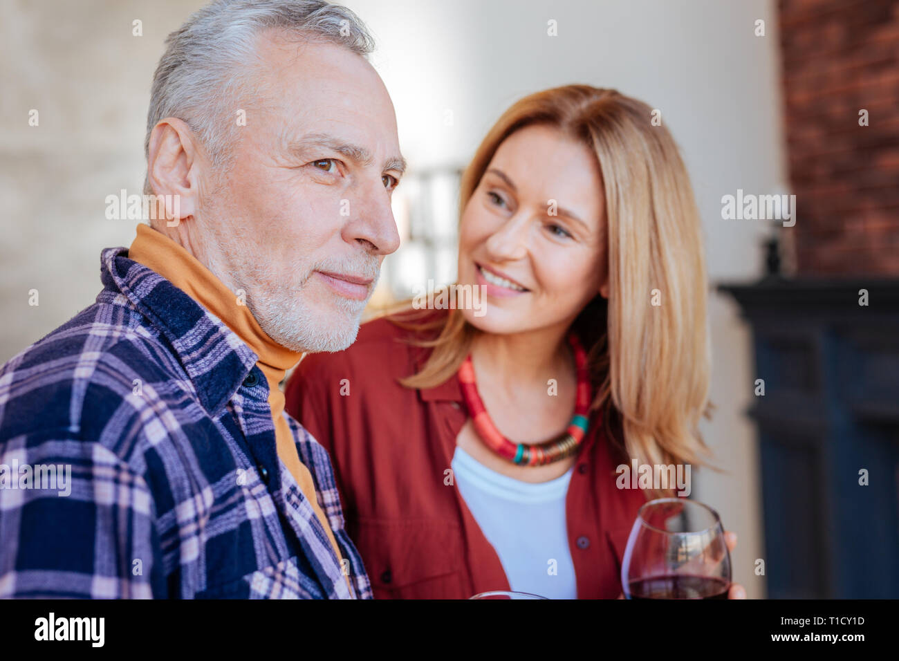 Wife wearing stylish necklace looking at handsome husband Stock Photo