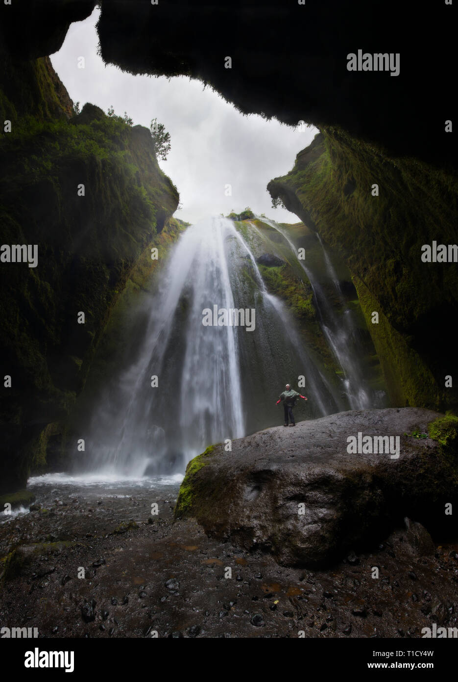travel to Iceland, person with raised hands standing in waterfall Gljufrabui, inspired happy traveler enjoying nature, adventure concept - Stock Image