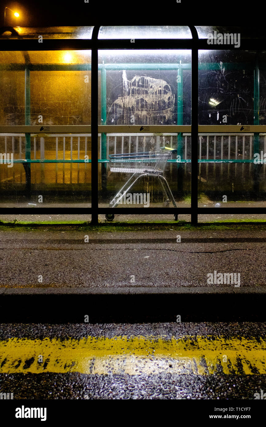 A shopping trolley lies abandoned inside a bus shelter on a wet scottish night - Stock Image
