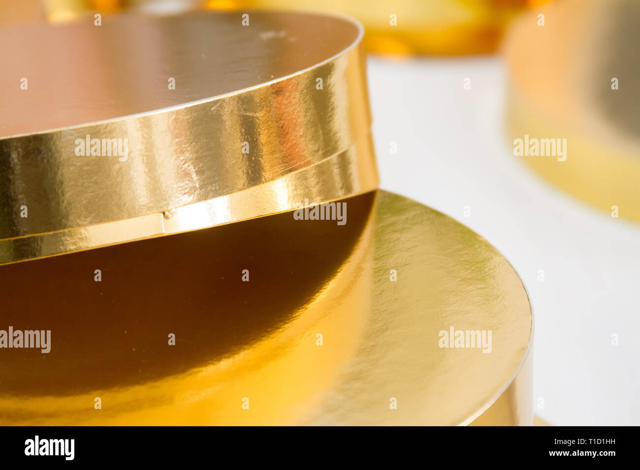 Gold and white coasters for cakes, rings for decorating cakes, baking tools, selektive focus - Stock Image