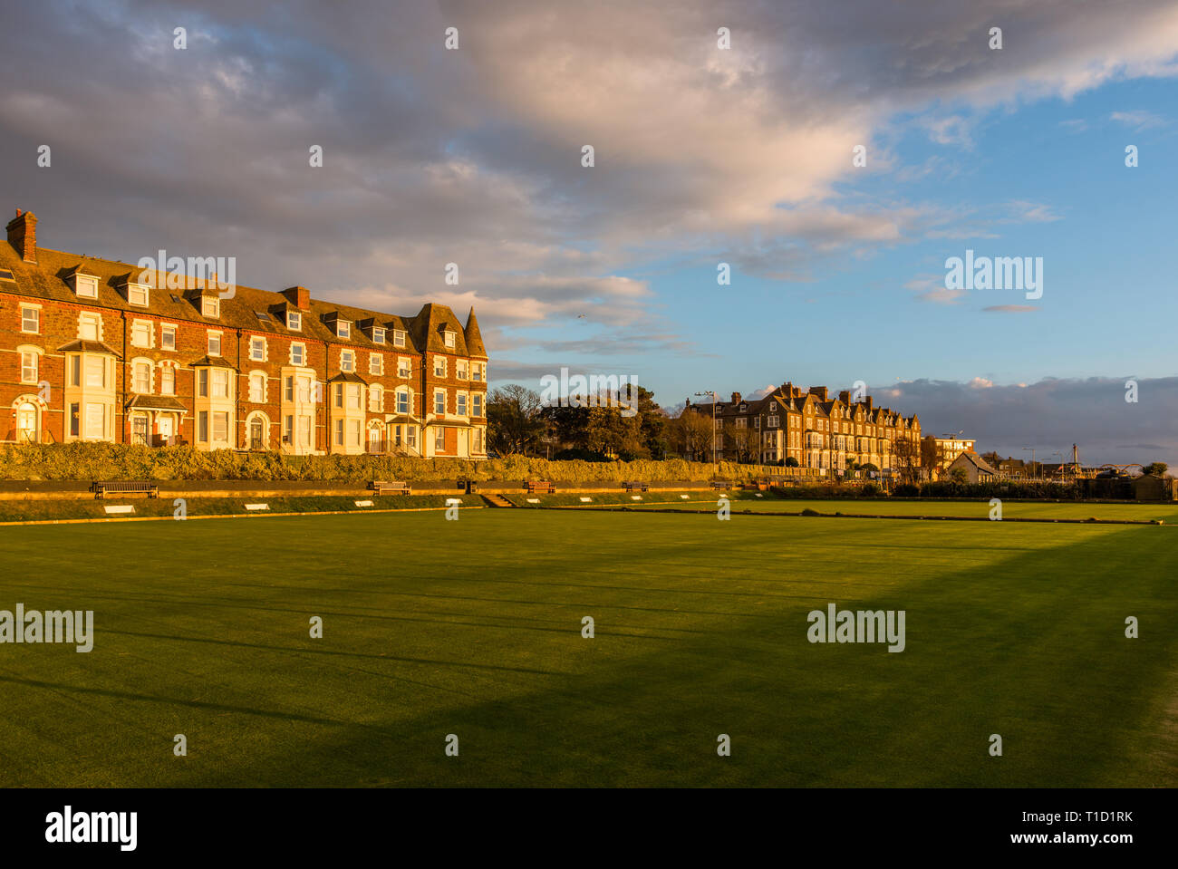 Cliff Parade bowling green and terrace of houses at Hunstanton warn late evening sun, Norfolk, East Anglia, England, UK. - Stock Image