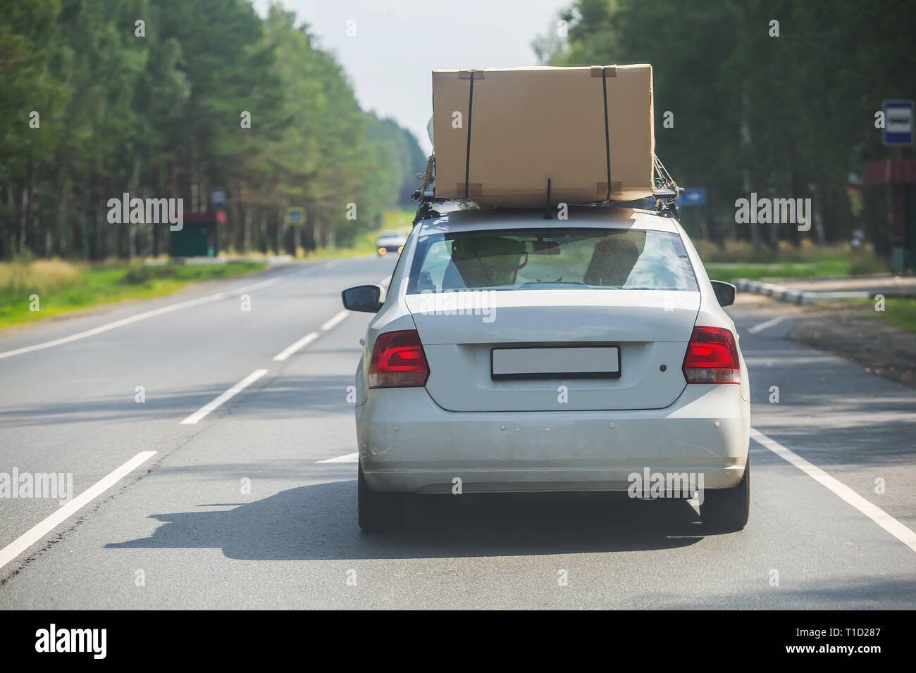 car with large cardboard box on the upper trunk is moving along the highway - Stock Image
