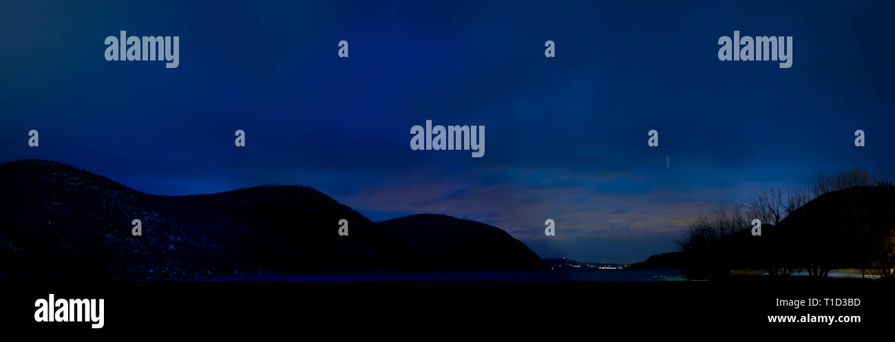 Panoramic View of Tail Lights of Airplane in Dark Blue Sky above Silhouetted Rolling Hills and Village Lights - Stock Image