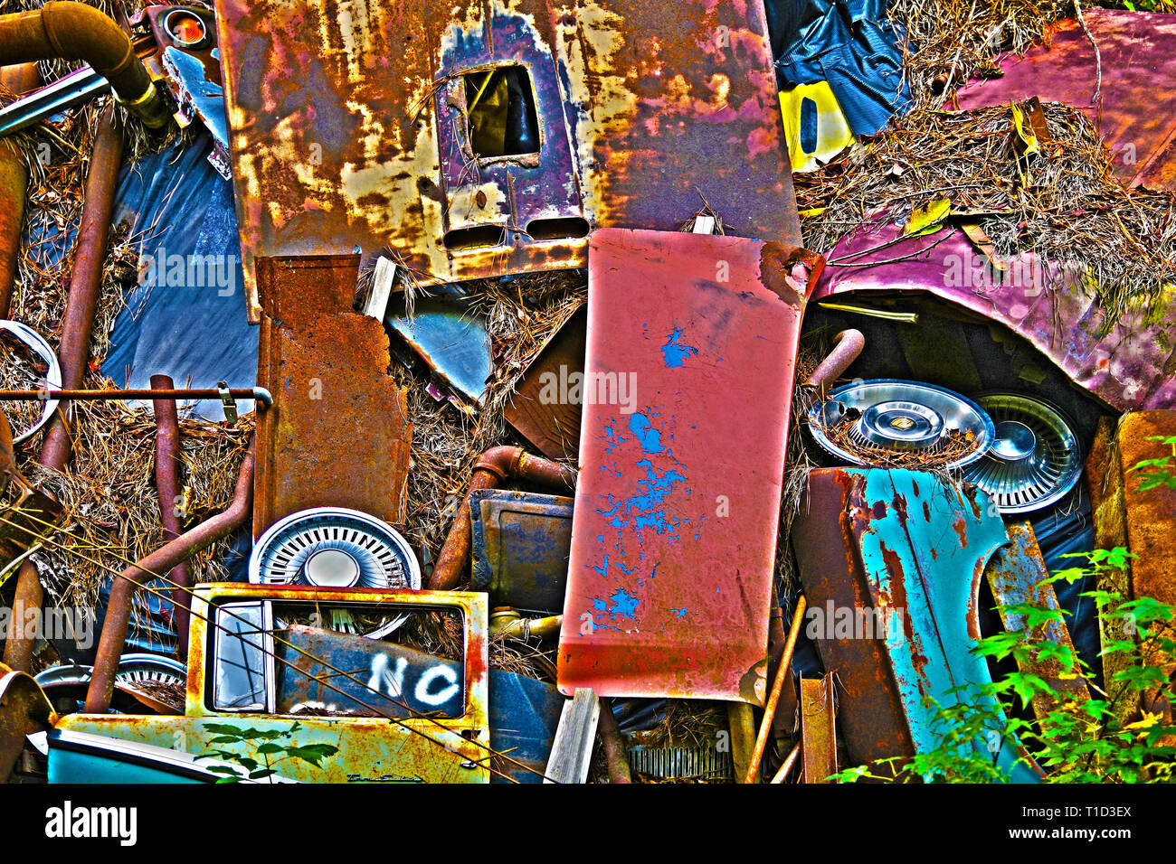A Pile of Scrap Metal with Various Car Parts and Other Items at a Junk Yard - Stock Image