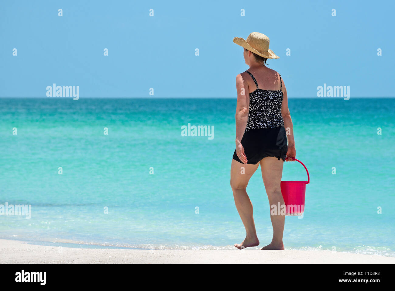 759529d8 Woman Walking on Gulf Coast Beach in Florida carrying a Red Beach Bucket -  Stock Image