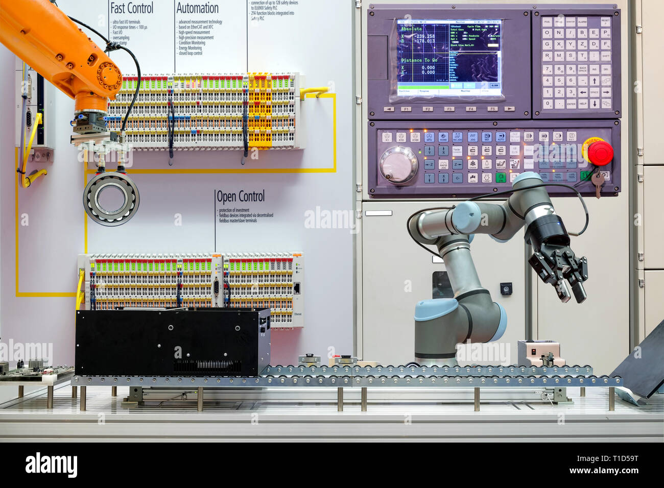 Industrial robotics working via conveyor belt on smart factory, terminal and control panel background, industry 4.0 concept Stock Photo