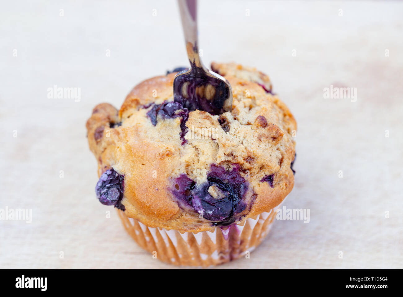 Homemade vegan blueberry muffin presented on a wooden plate Stock Photo