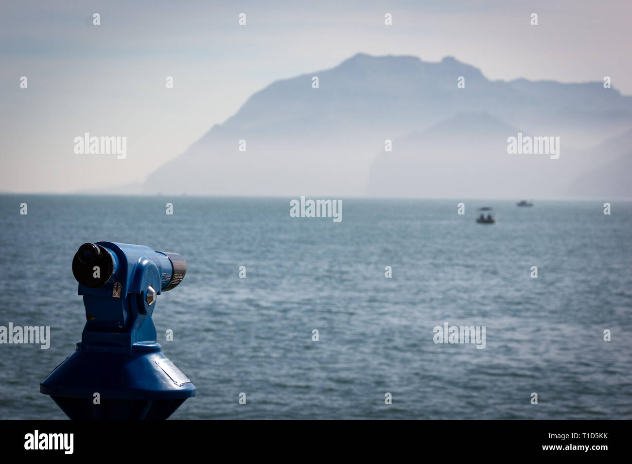 Background of a blue panoramic touristic telescope overlooking the Mediterranean sea with a boat. - Stock Image