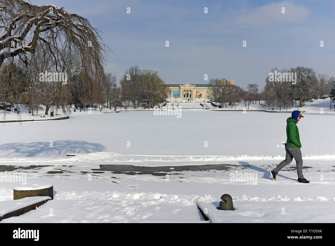 A solitary man walks around the snow-covered pond outside the Cleveland Museum of Art during the winter in Cleveland, Ohio, USA. Stock Photo