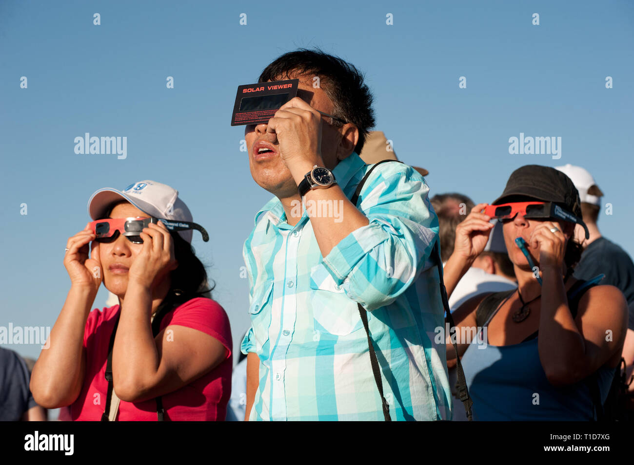 Visitors to Arches National Park viewing the 2012 solar eclipse through special glasses - Stock Image