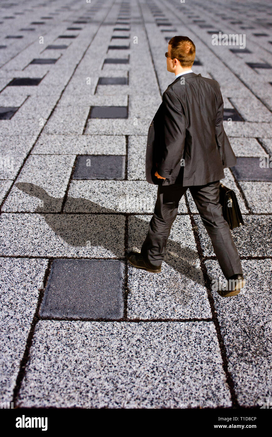 man in suit and briefcase walking - Stock Image