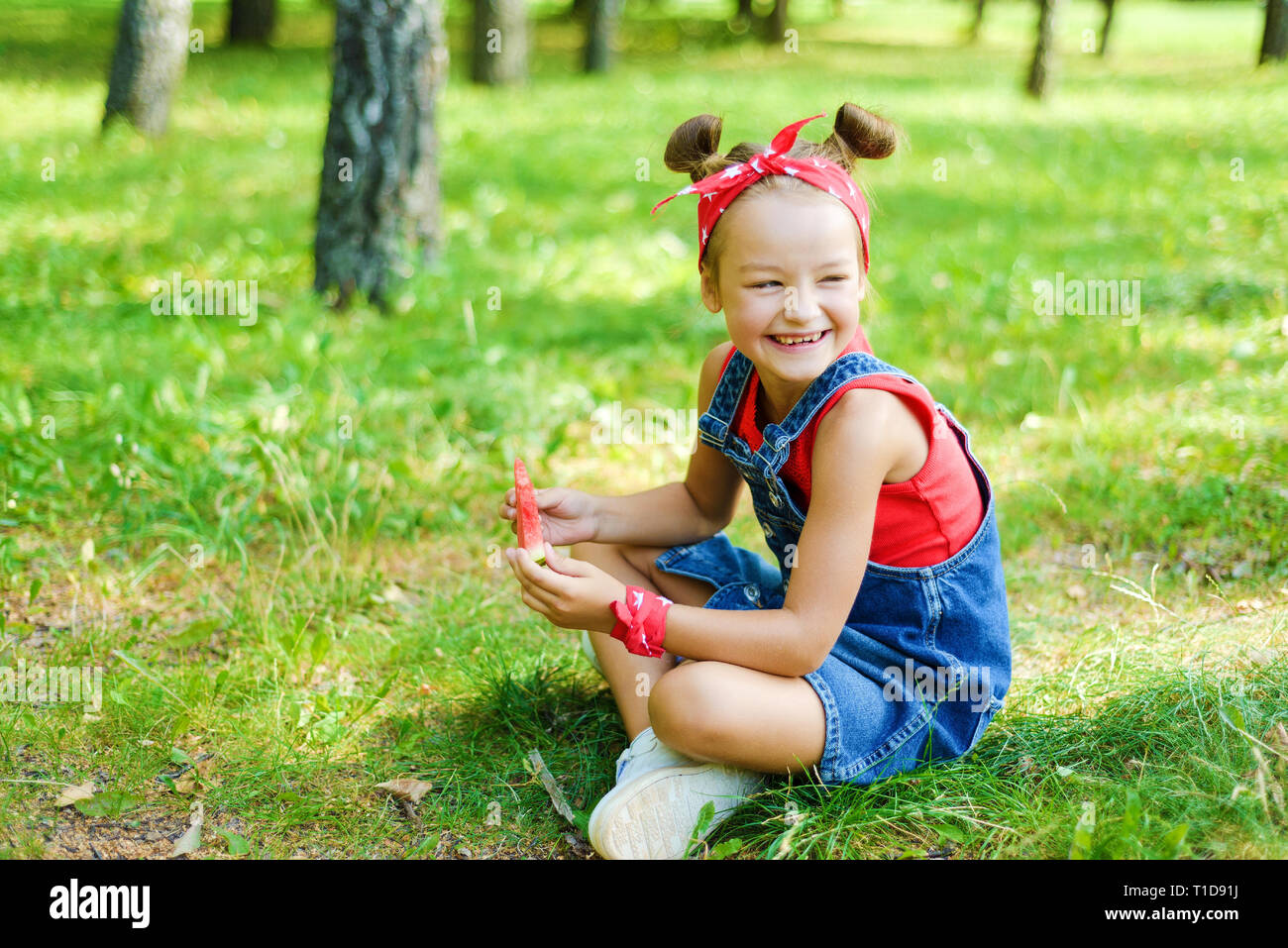 c13187633fce happy little girl in red T-shirt and headscarf in denim overalls holding  ripe watermelon and laughing. the child is sitting on the grass in the park