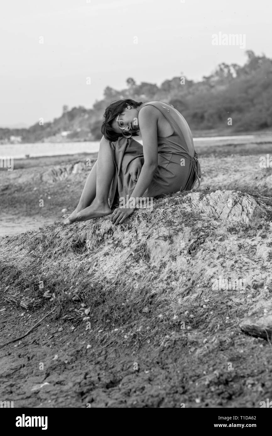 Black and white photo of a girl in a dress sitting on the ground. - Stock Image