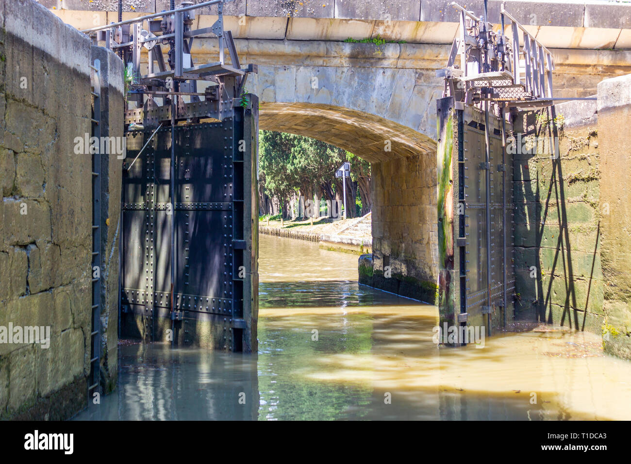 Lock gates opening on the Canal du Midi at its pass through Carcasonne, Aude, Occitanie, France. - Stock Image