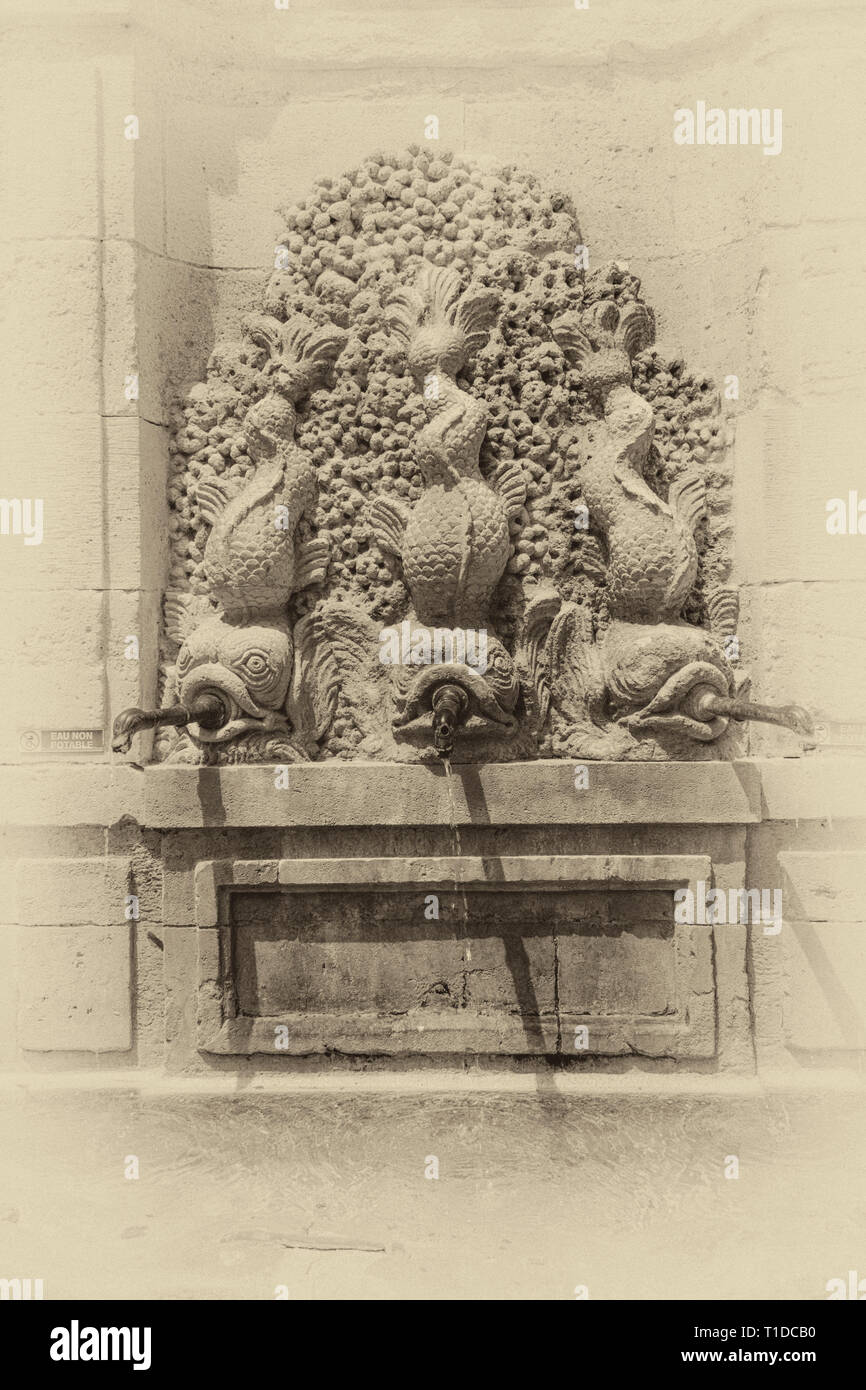 Narbonne, Occitanie region, France.  Fountain with three fishes spouting water. - Stock Image
