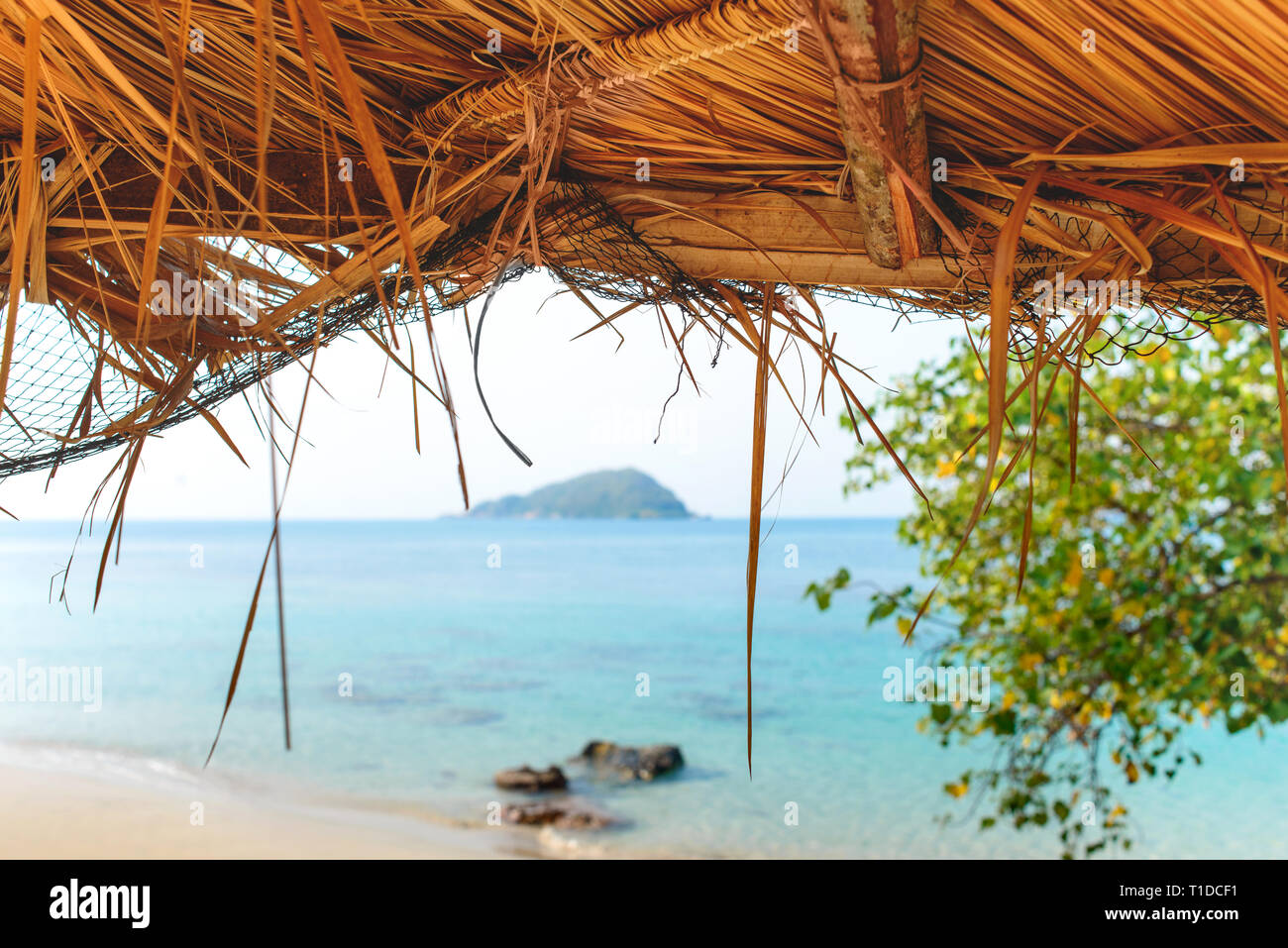 Tropical sand beach sea shore view through the straw umbrella roof. Travel vacation summer. - Stock Image