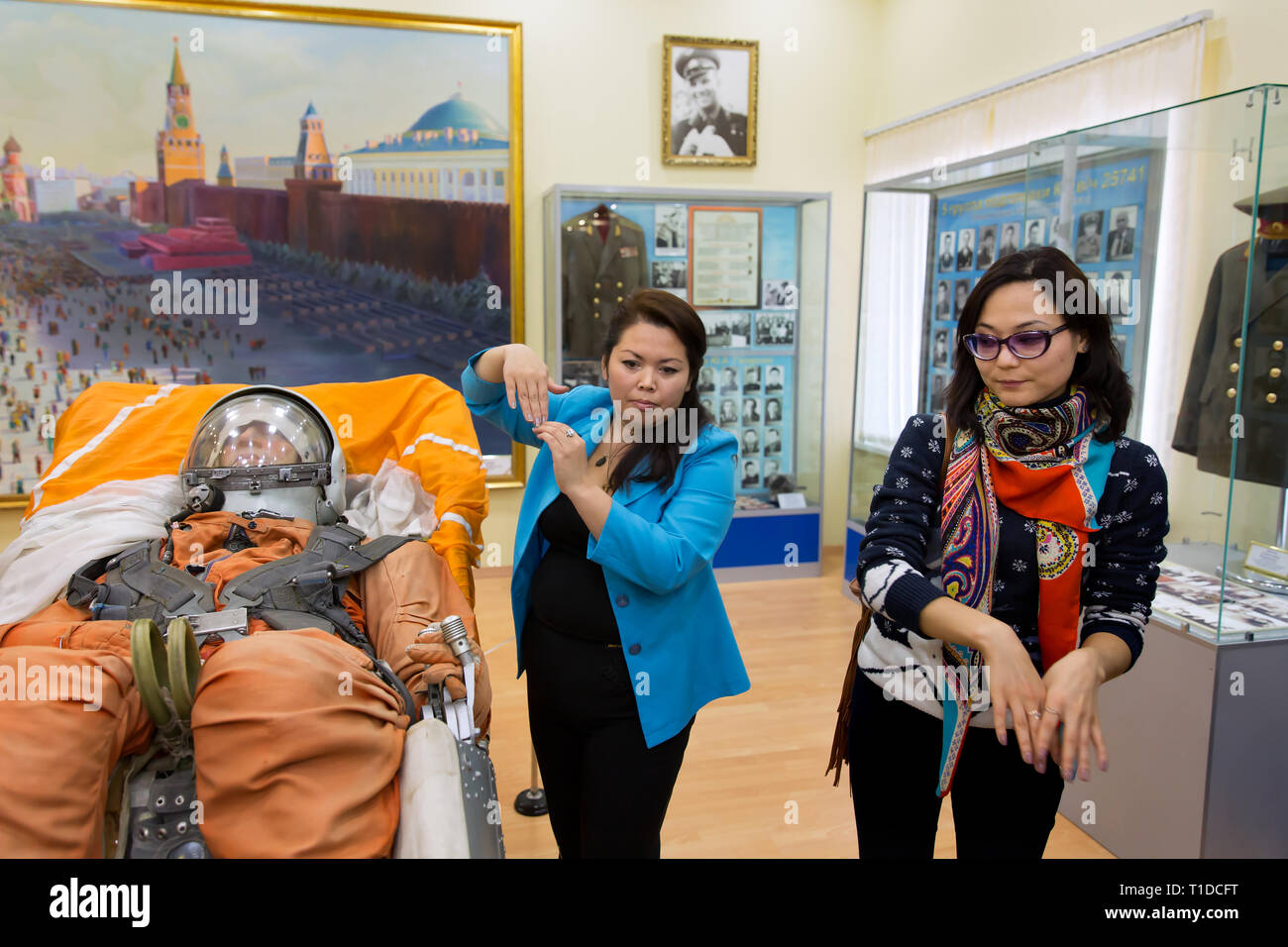 BAIKONUR - Kazakh museum and tour guides explain the working of an ejection seat of the Vostok spacecraft in the Cosmodrome museum. - Stock Image