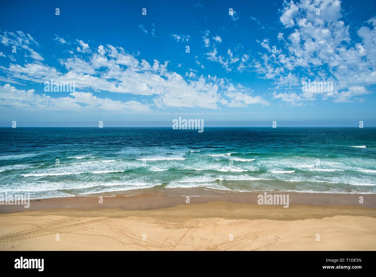Yellow sand beach, sea and deep blue sky - Stock Image