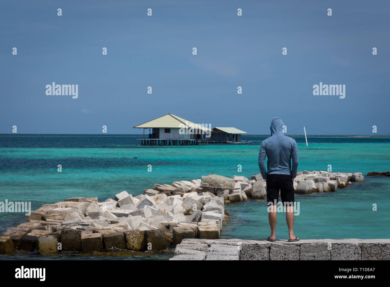 A man with navy jacket and short pants standing and looking to floating house and scattered stones with beautiful turquoise ocean water at Harapan Isl Stock Photo