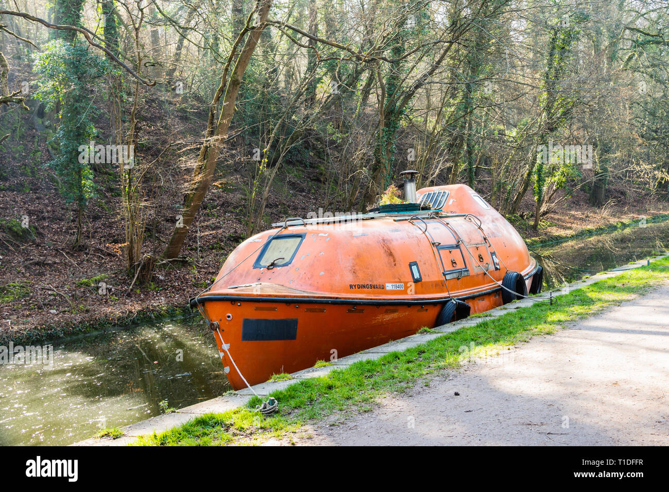 A fully enclosed freefall lifeboat has been converted into a houseboat and is seen moored on the Kennet and Avon canal Stock Photo