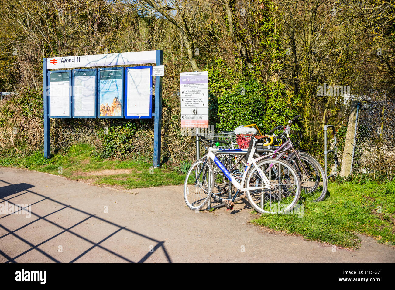 An entrance to Avoncliff railway station with a notice board and several bicycles secured to a metal railing Stock Photo
