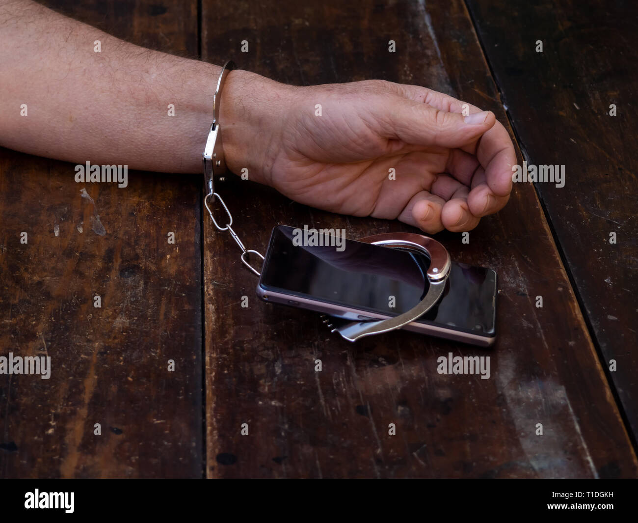A man handcuffed to a smartphone. Smartphone or internet addiction concept - Stock Image