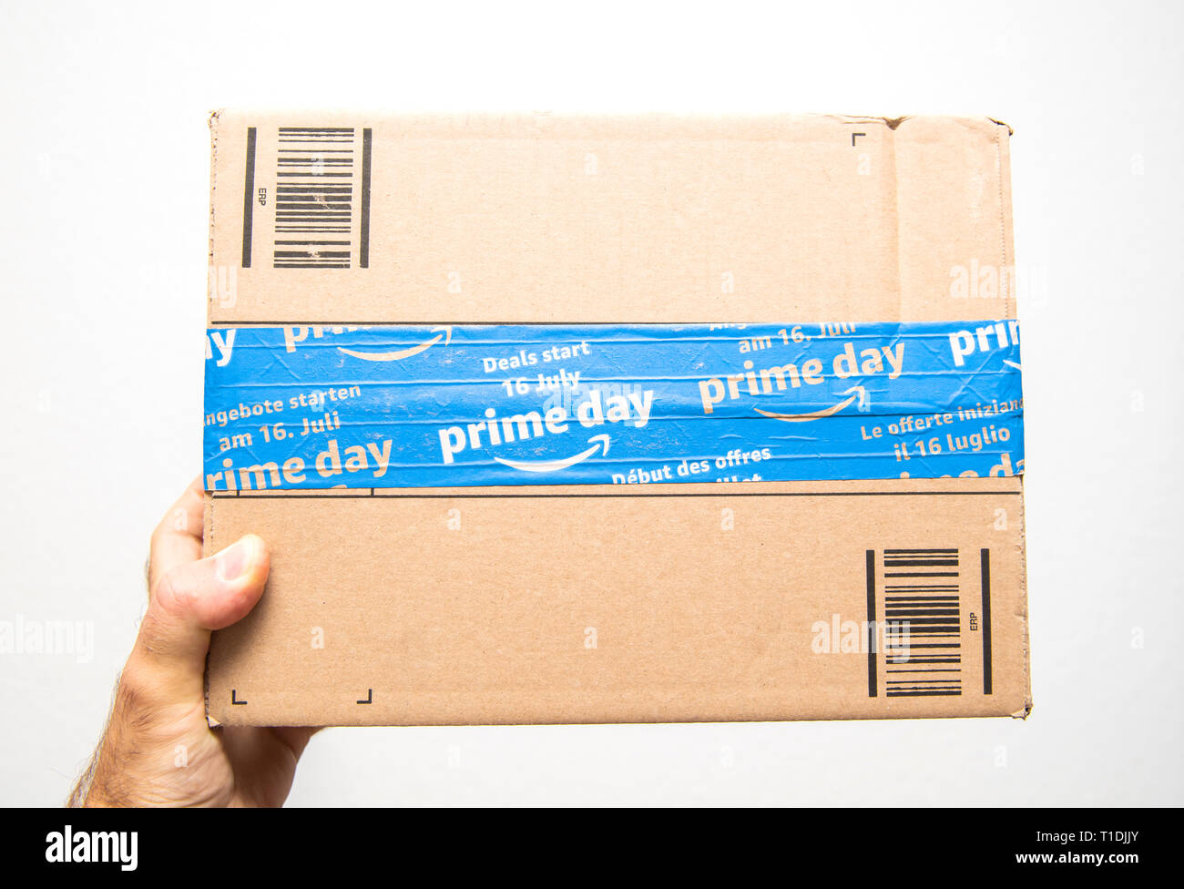 Paris, France - Jul 11, 2018: Man hand holding against white background sealed with special scotch tape of Amazon Prime parcel delivery - Stock Image