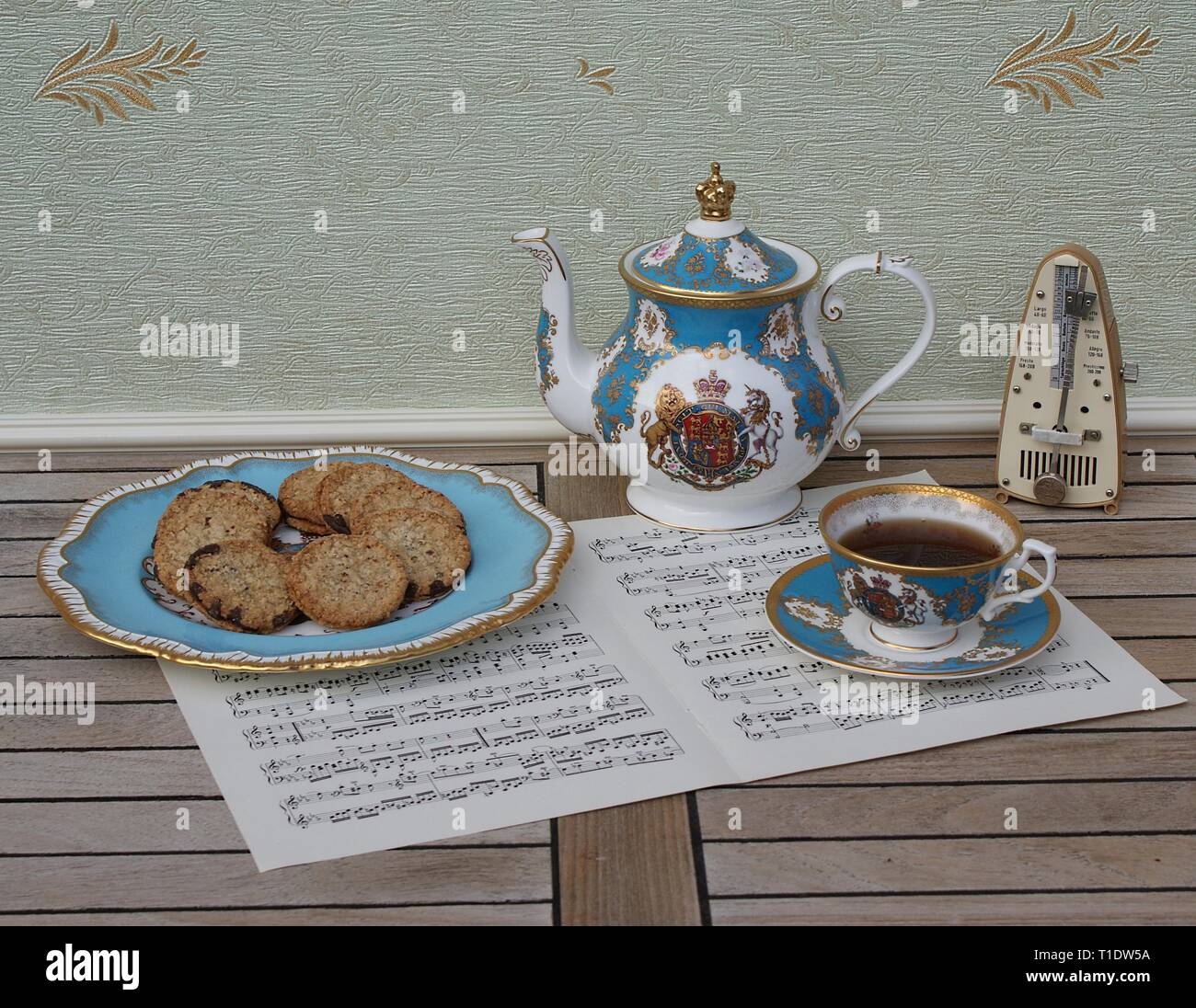 English teacup with saucer, teapot and a cake plate with cookies, fine bone china porcelain, and a metronome for music on a sheet of music - Stock Image