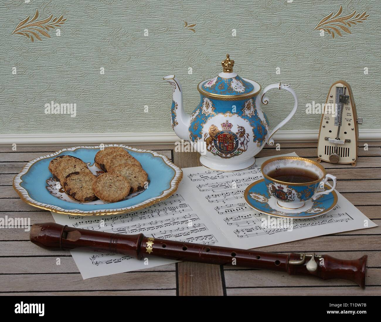 English teacup with saucer, teapot and a cake plate with cookies, fine bone china porcelain, metronome for music and a block flute on a sheet of music - Stock Image