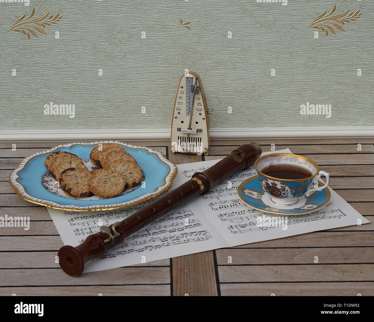 English teacup with saucer and a cake plate with cookies, fine bone china porcelain, metronome for music and a block flute on a sheet of music - Stock Image