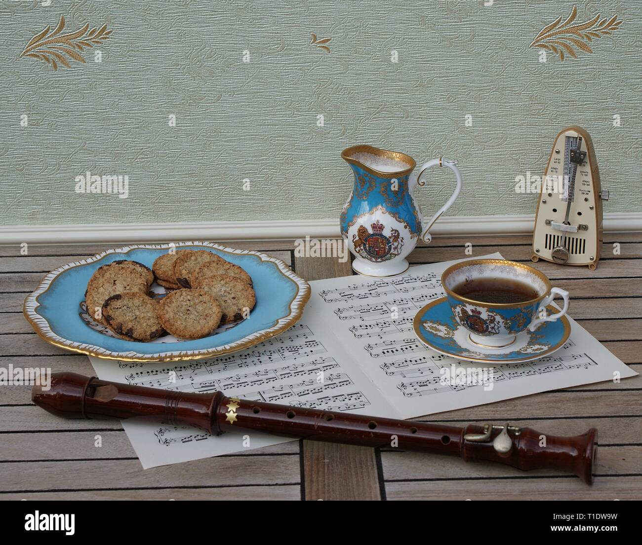 English teacup with saucer, cream jug and a cake plate with cookies, fine bone china porcelain, metronome for music, a block flute on a sheet of music - Stock Image