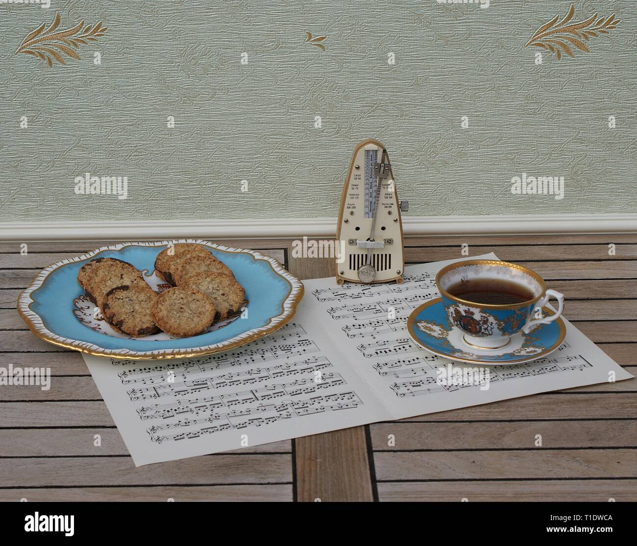 English teacup with saucer and a cake plate with cookies, fine bone china porcelain, and a metronome for music on a sheet of music - Stock Image