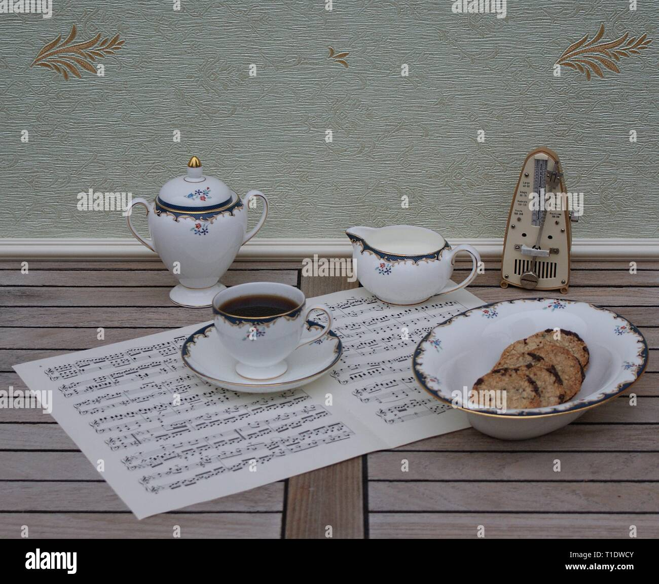 English teacup with saucer, cream jug, sugar bowl and a cake bowl, fine bone china porcelain, and a metronome for music on a sheet of music - Stock Image