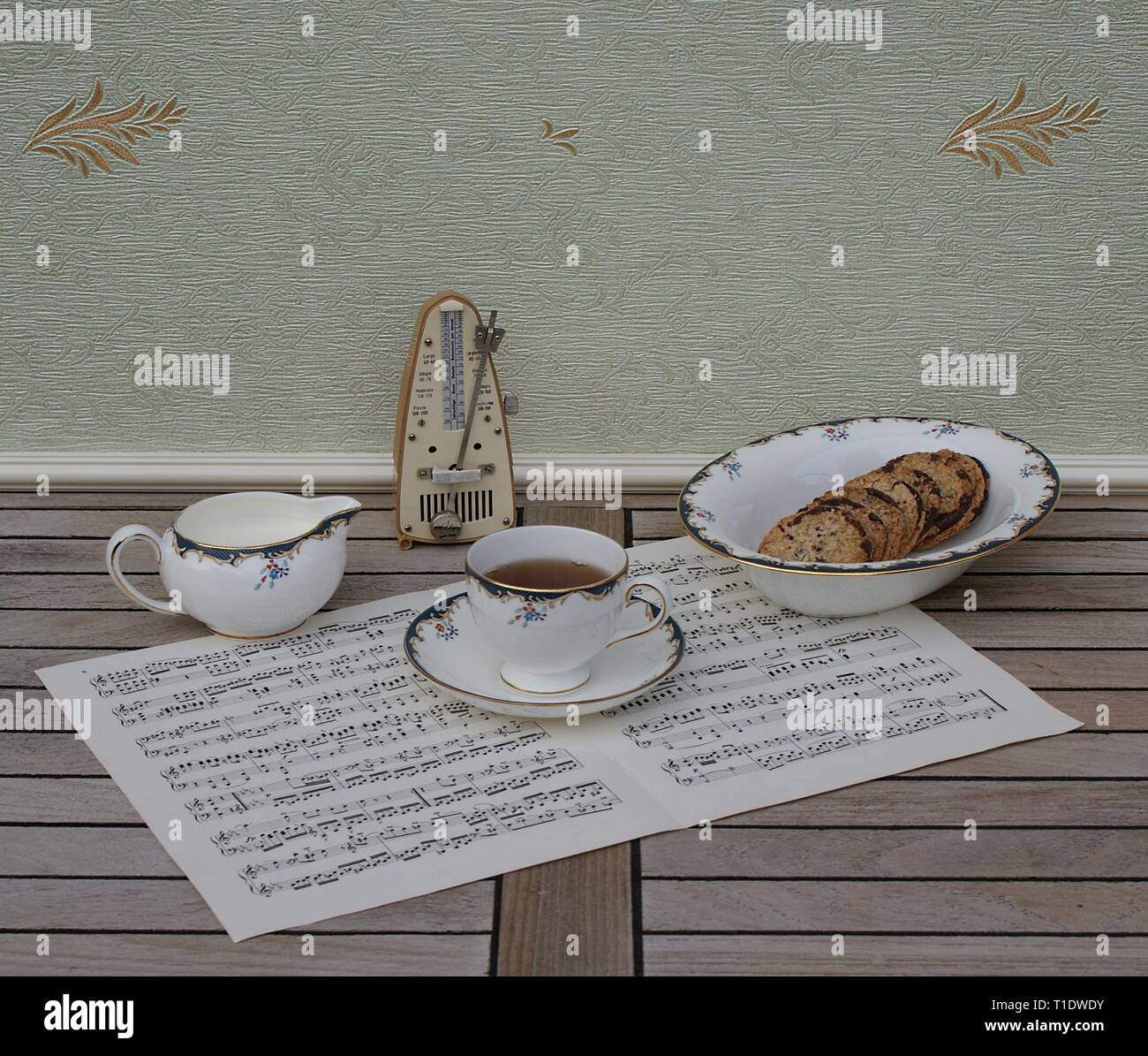 English teacup with saucer, cream jug  and a cake bowl, fine bone china porcelain, and a metronome for music on a sheet of music - Stock Image