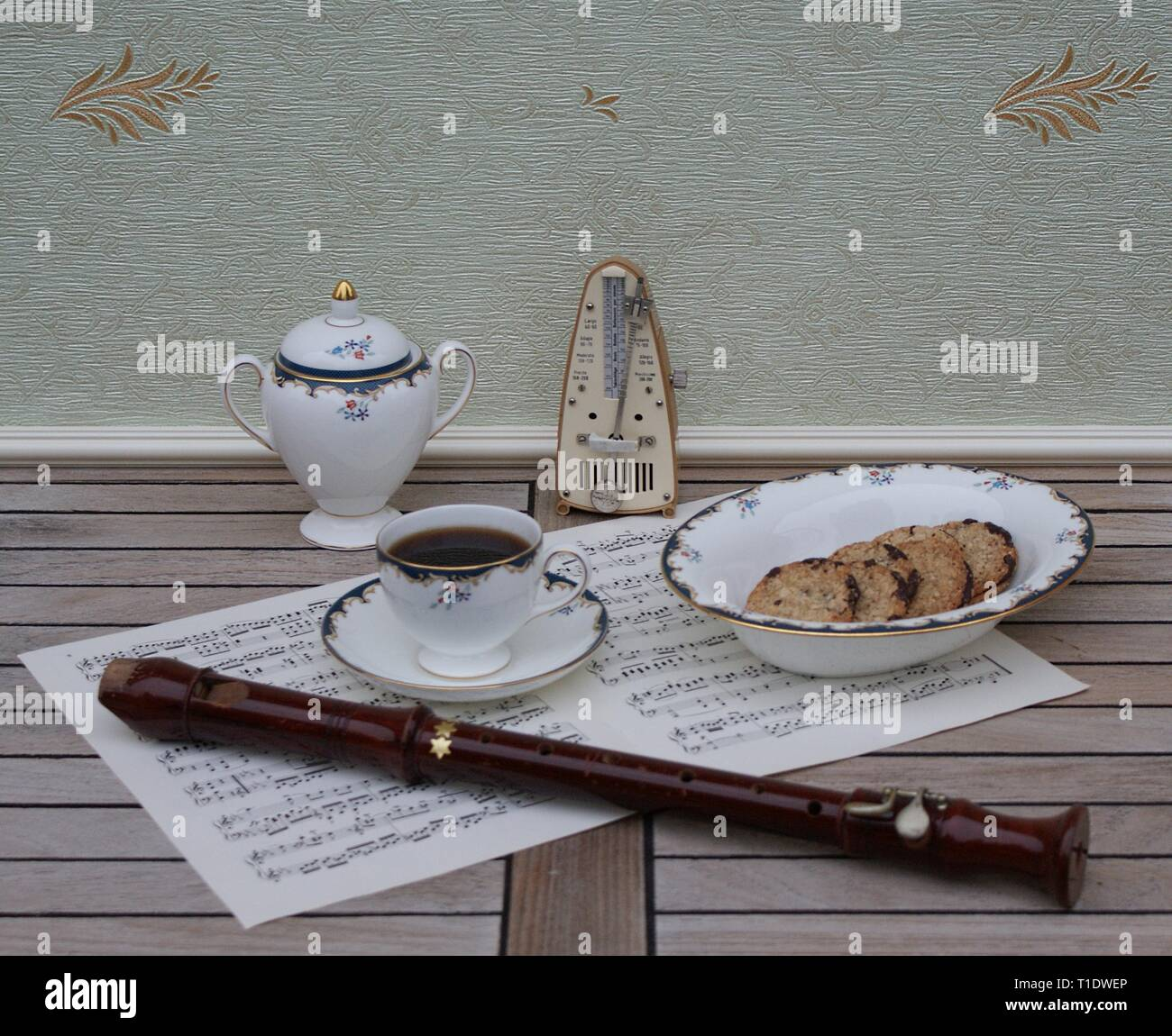 English teacup with saucer, sugar bowl and a cake bowl, fine bone china porcelain, metronome for music and a block flute on a sheet of music - Stock Image