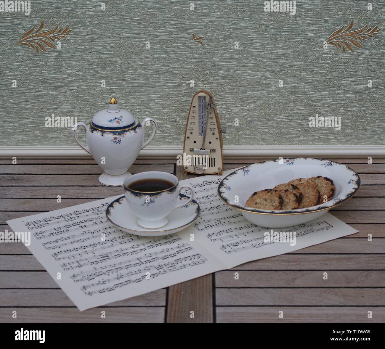 English teacup with saucer, sugar bowl and a cake bowl, fine bone china porcelain, and a metronome for music on a sheet of music - Stock Image