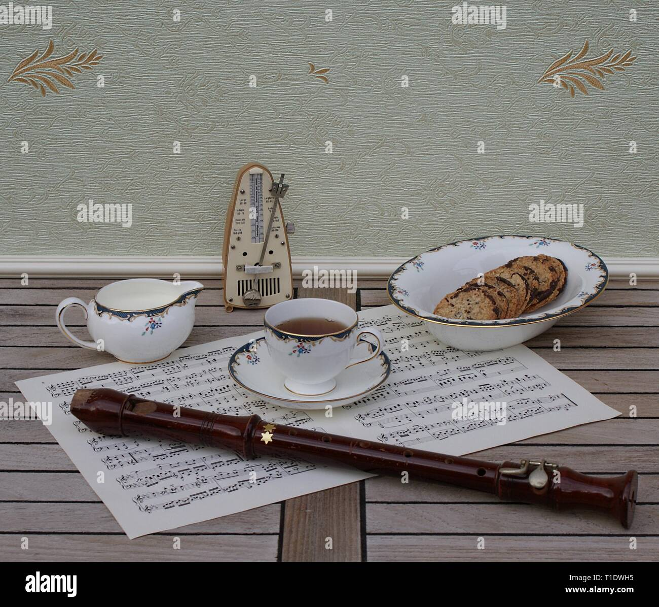 English teacup with saucer, cream jug and a cake bowl, fine bone china porcelain, metronome for music and a block flute on a sheet of music - Stock Image