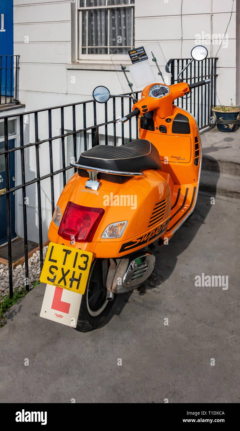 Close up Rear view of a Bright orange motor scooter parked outside a house front door - Stock Image