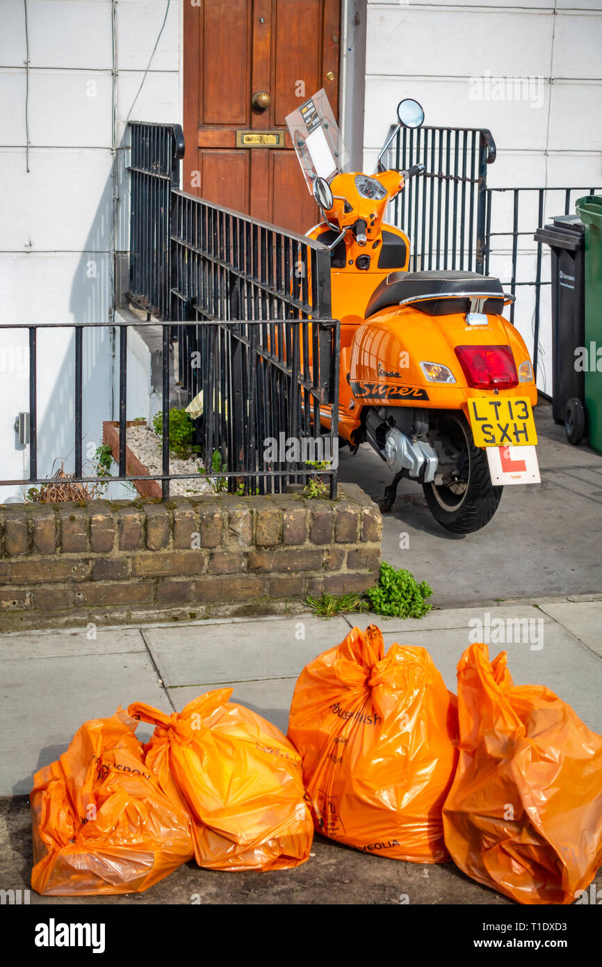 Rear view of a Bright orange motor scooter parked outside a house front door with four orange recycle bags in front of the bike and house - Stock Image