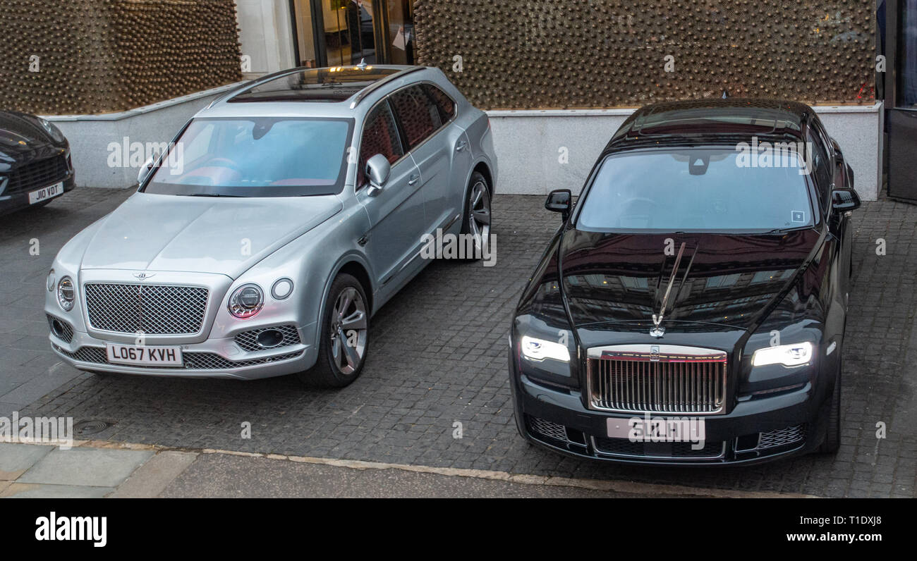 one black Rolls Royce and a silver Bentley Bentayga two executive cars parked in VIP parking area outside a top London Hotel - Stock Image