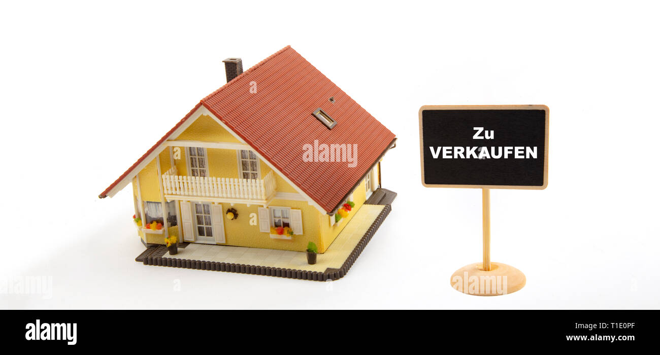 Zu Verkaufen means For Sale. Concept Business Real Estate with Toy House and little Blackboard Sign on white Background - Stock Image