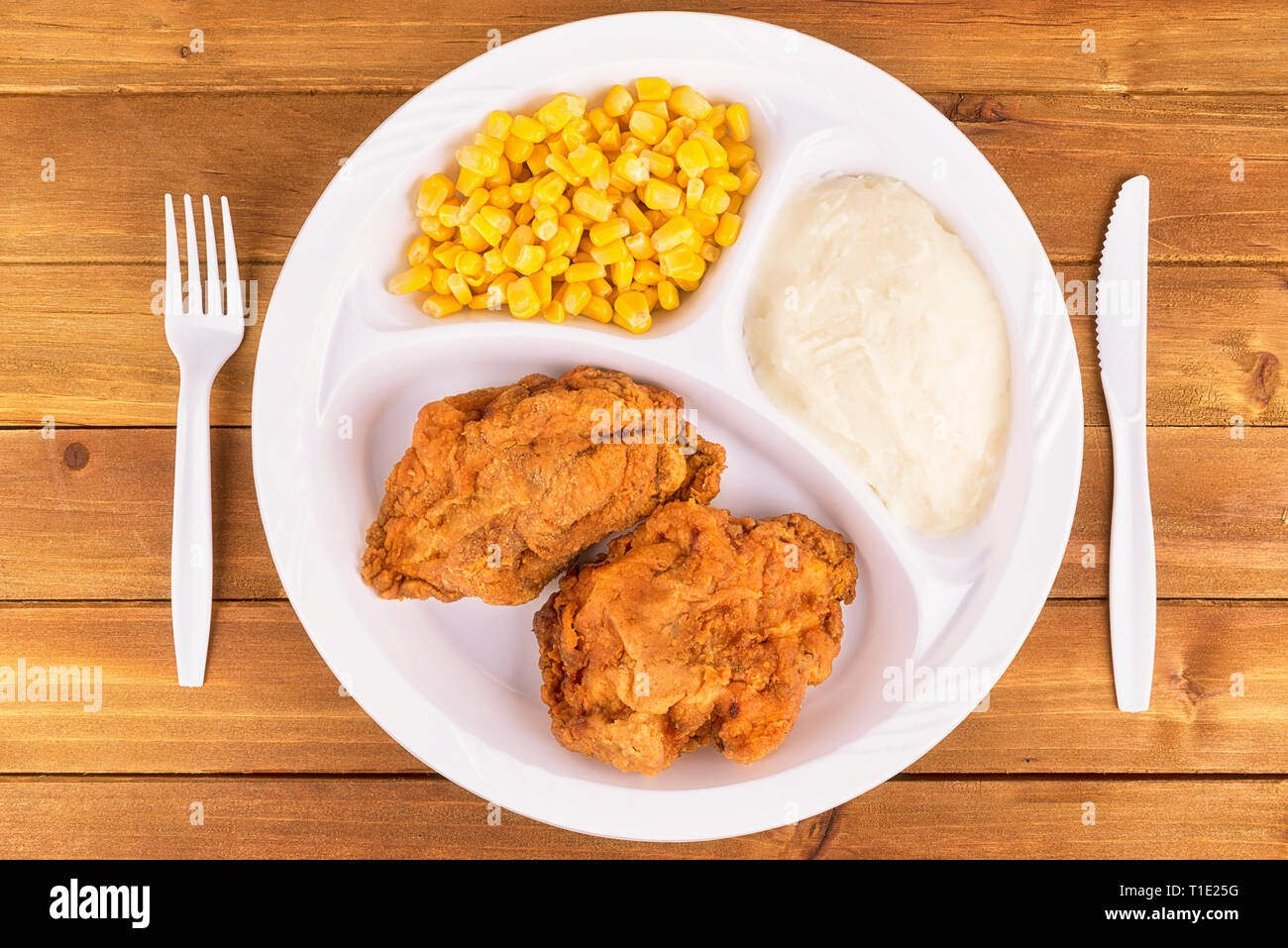 Fried chicken tv dinner on wooden background, top view. - Stock Image
